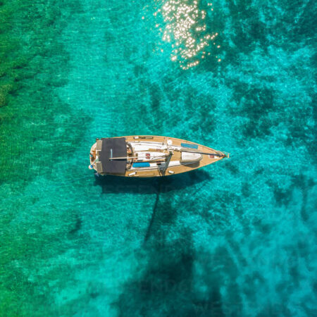 Aerial view of one sailing boat anchored on transparent coast, Ithaki, Greece